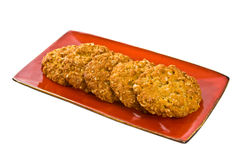 Anzac Cookies. Traditional Australian Anzac Biscuits on red plate isolated over white background stock photo