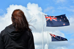 Anzac Day services. A New Zealander person (woman) under the national flags of Australia and New Zealand during a National War Memorial Anzac Day services in New stock photo