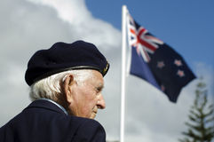 Anzac Day - War Memorial Service. MANGONUI, NEW ZEALAND - APRIL 25 2012: NZ veteran soldier stands under New Zealand flag at the National War Memorial on April Stock Image