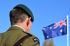 Anzac Day - War Memorial Service. MANGONUI, NEW ZEALAND - APRIL 25 2014: New Zealand Army officer stands under New Zealand flag during the National War Memorial Stock Photography