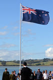 Anzac Day - War Memorial Service. MANGONUI, NEW ZEALAND - APRIL 25 2014: Young New Zealander man is lowering the flag of New Zealand during the National War Royalty Free Stock Photography