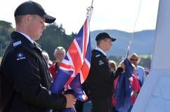 Anzac Day - War Memorial Service. MANGONUI, NEW ZEALAND - APRIL 25 2014: Young New Zealander men lowering the flags of New Zealand and Australia during the Stock Image