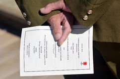 Anzac Day - War Memorial Service. New Zealand Army veteran soldier hands holds  ANZAC order of service during a National War Memorial Anzac Day in New Zealand Stock Images