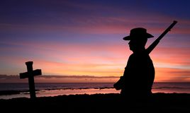 ANZAC Soldier with Cross at Sunrise. A silhouette of an Australian soldier in AIF first world war uniform and 303 rifle with cross at sunrise near the beach with royalty free stock photo