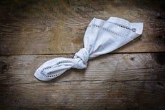 Anzeige, Knoten im Taschentuch des weißen Stoffes auf einem rustikalen hölzernen stockfoto