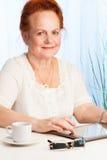 Anziana sorridente con il pc del ridurre in pani Fotografia Stock Libera da Diritti