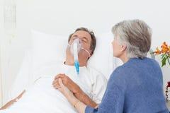 Anziane che catturano cura del suo marito Immagine Stock