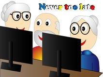 Anziani al corso di tecnologia dell'informazione che si siede ad un computer portatile Immagine Stock