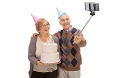 Anziani allegri con i cappelli e la torta di compleanno del partito che prendono un selfie Immagini Stock Libere da Diritti