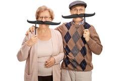 Anziani allegri con i grandi baffi falsi Fotografie Stock