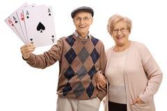Anziani allegri con quattro carte da gioco degli assi Immagini Stock