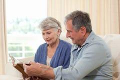 Anziani che esaminano il loro album di foto Fotografie Stock