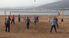 Anziani che giocano nella pallavolo sulla spiaggia video d archivio