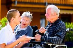 Anziani che mangiano caramella in giardino della casa di cura Fotografie Stock