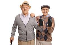 Anziani che mostrano i telefoni alla macchina fotografica Fotografie Stock