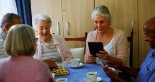 Anziani che per mezzo del telefono cellulare e della compressa digitale mentre giocando scacchi 4k video d archivio
