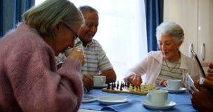 Anziani che per mezzo del telefono cellulare e della compressa digitale mentre giocando scacchi 4k archivi video