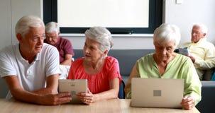 Anziani che per mezzo della compressa digitale e del computer portatile archivi video