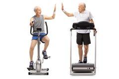 Anziani che si esercitano su una bici fissa e su una pedana mobile alte--fiv Fotografie Stock Libere da Diritti
