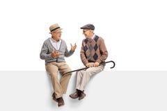 Anziani che si siedono su un pannello e su una conversazione Immagini Stock