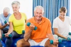 Anziani che usando la palla ed i pesi di esercizio fotografia stock