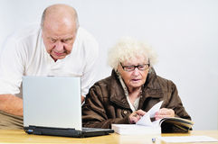 Anziani con il computer portatile fotografia stock