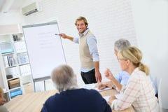 Anziani d'aiuto dell'istruttore di affari nella classe Immagine Stock