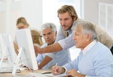 Anziani d'aiuto dell'istruttore nella classe di informatica Fotografie Stock