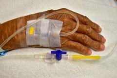 Anziani della mano con IV il gocciolamento fotografie stock libere da diritti