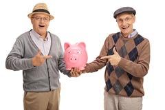 Anziani felici che tengono un porcellino salvadanaio ed indicare Immagini Stock Libere da Diritti