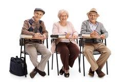 Anziani nelle sedie della scuola che prendono le note Immagini Stock