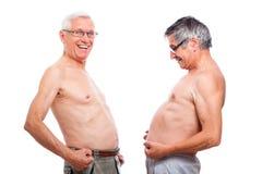 Anziani nudi divertenti che confrontano pancia Immagini Stock