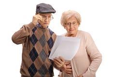 Anziani sorpresi che esaminano i documenti Immagine Stock Libera da Diritti