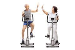 Anziani sulle bici di esercizio alte--fiving fotografia stock libera da diritti