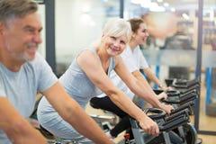 Anziani sulle bici di esercizio nella classe di filatura alla palestra Immagini Stock