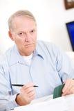 Anziani: Uomo senior stanco delle fatture di pagamento Fotografia Stock Libera da Diritti
