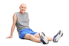 Anziano in abiti sportivi che si siedono sul pavimento e sul riposo Fotografia Stock Libera da Diritti