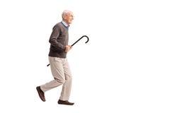 Anziano allegro che porta una canna e un funzionamento Immagine Stock