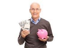 Anziano allegro che tiene alcune pile di soldi Fotografie Stock