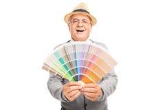 Anziano allegro che tiene un campione della tavolozza di colore Fotografia Stock