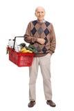 Anziano allegro che tiene un cestino della spesa Immagini Stock Libere da Diritti