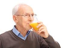 Anziano che beve un succo d'arancia Fotografie Stock Libere da Diritti