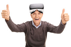Anziano che dà i pollici su dopo avere per mezzo di una cuffia avricolare di VR Fotografia Stock Libera da Diritti