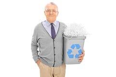 Anziano che giudica un recipiente di riciclaggio pieno di carta tagliuzzata Fotografia Stock
