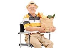 Anziano che giudica una borsa di drogheria messa in sedia a rotelle Immagini Stock