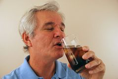 Anziano che gode di una cola fredda Fotografie Stock