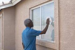 Anziano che lava una finestra domestica Fotografia Stock Libera da Diritti
