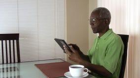 Anziano che lavora con una compressa a casa in Arizona video d archivio