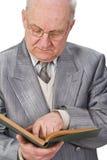 Anziano che legge un libro Immagini Stock