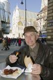 Anziano che mangia la salsiccia a Vienna, Austria fotografie stock libere da diritti